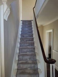 wooden staircase with grey carpet